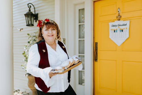 Photo Of Woman Holding A Tray Of Doughnuts