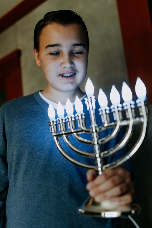 Photo Of Boy Holding A Candle Holder