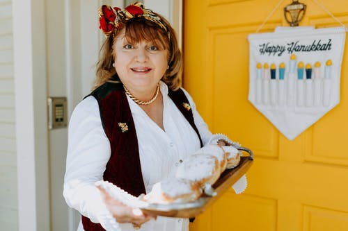 Photo Of Woman Carrying A Tray Of Fresh Doughnuts