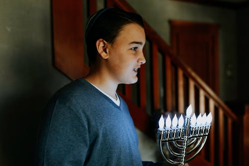 Photo Of Boy Carrying Candle Holder