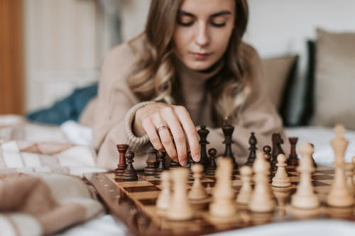 A Woman Playing a Board Game of Chess