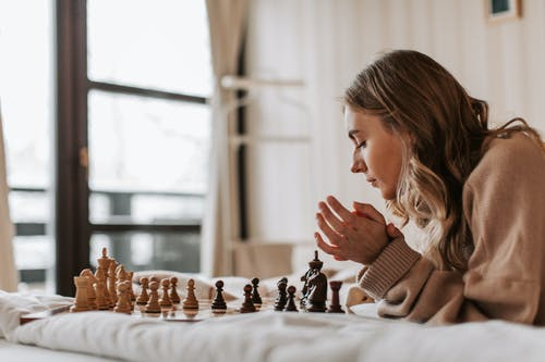 A Woman Playing Chess in Bed