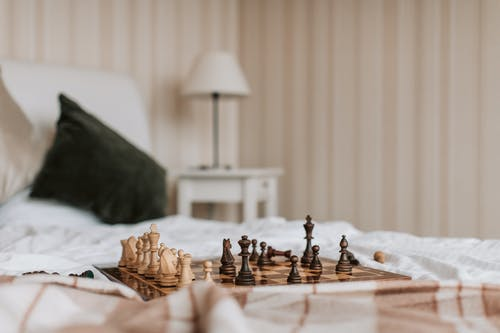 Chess Pieces on Brown Wooden Chess Board