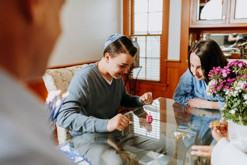 Photo Of Family Playing Dreidel Together