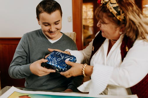彼女の息子に贈り物を渡す母親の写真