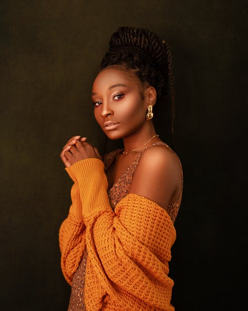 Side view of calm black woman with afro braids wearing orange cardigan standing with clasped hands and looking at camera on dark background