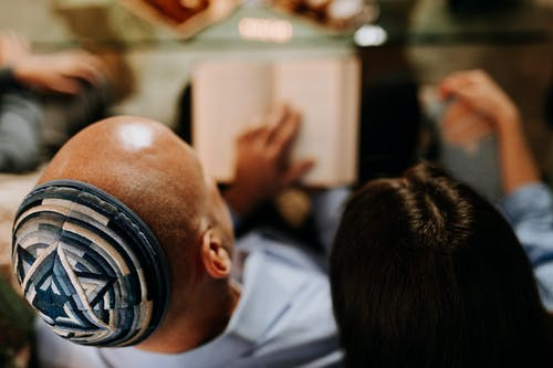 Photo Of Man Reading For His Family