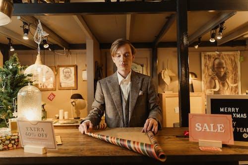Man in Gray Suit Jacket Standing Beside Brown Wooden Table