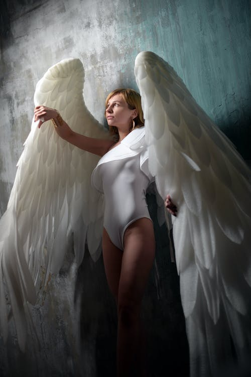 Feminine young lade wearing white bodysuit and big angle wings while standing against gray wall in studio and looking away dreamily