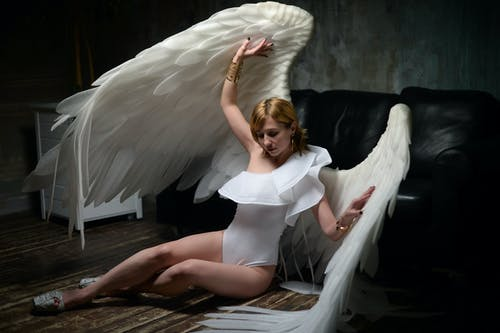 Full body of young slim female model in white bodysuit and artificial angel wings sitting on wooden floor in dark room