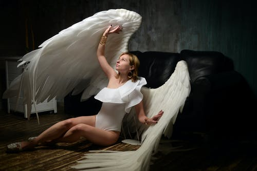 Feminine young woman in with white angel wings sitting on floor