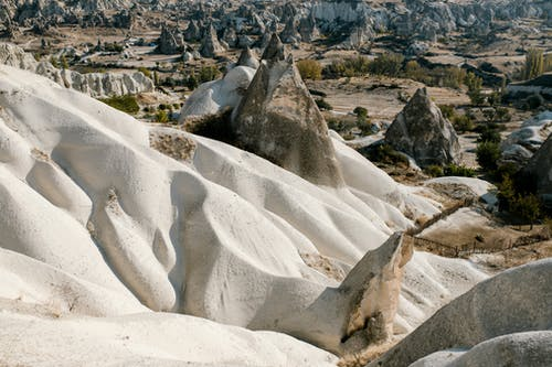 Scenery view of massive rocky formation with smooth curvy slopes located on highlands with many rough volcanic peaks in Cappadocia