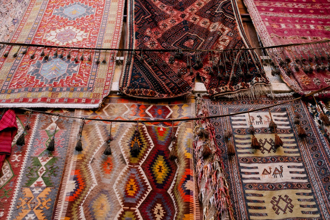 Colorful handmade weaved with oriental ornament middle east rugs hanging in open market
