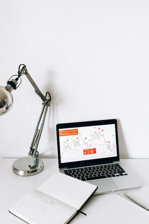 Macbook Pro Beside Silver Desk Lamp