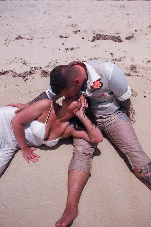 Man Kissing Woman on Beach