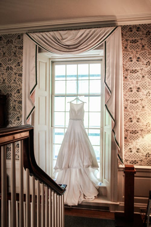 White Wedding Gown on Brown Wooden Piano