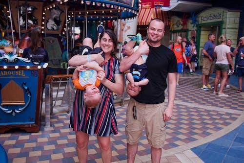 Man in Black Crew Neck T-shirt Holding Baby in Blue Onesie