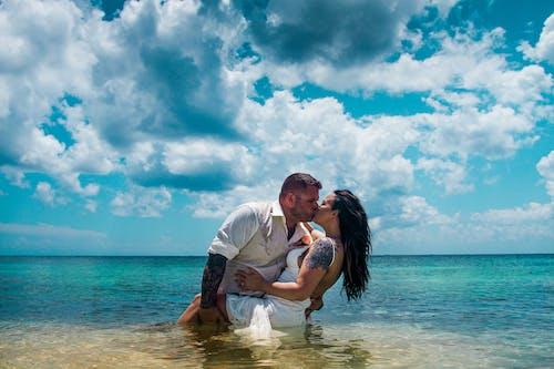 Man in White Shirt Kissing Woman in White Dress on Beach