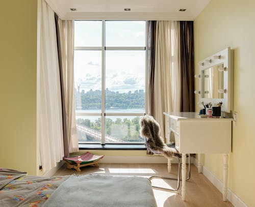 Interior of contemporary bedroom with large window with curtains and makeup mirror in daylight