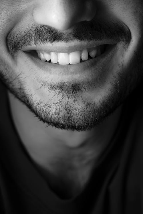 Black and white closeup of crop anonymous male with beard and mustache wearing casual t shirt