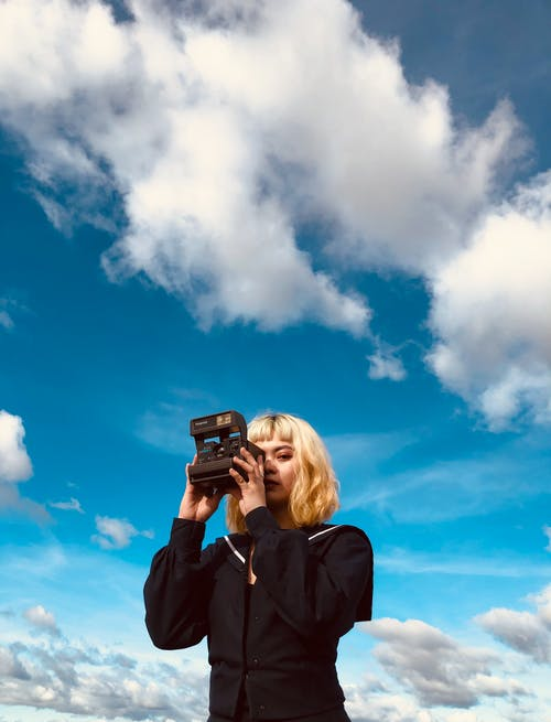 Low angle of young blond lady in trendy black outfit standing under blue cloudy sky with vintage photo camera in hands in daylight