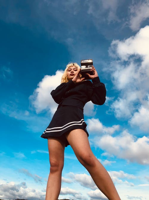 Low angle of cool Asian lady in black outfit standing with instant photo camera in hands and looking at camera under blue cloudy sky in daylight