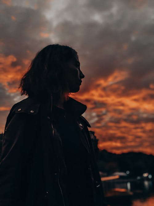 Woman in Black Coat Standing during Sunset