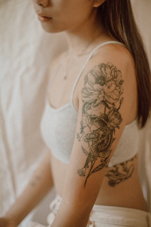 Side view of crop anonymous female with tattoo in lingerie resting in room with white fabric