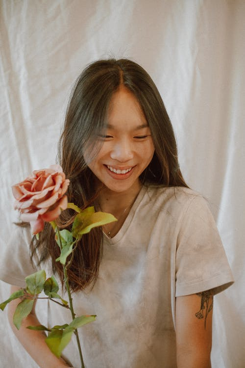 Happy Asian woman with rose smiling