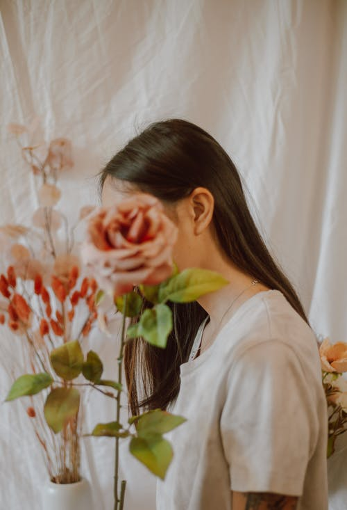 Slender woman in casual outfit with tender pink roses