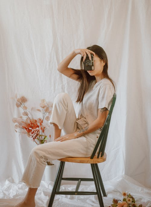 Side view of slender anonymous female in casual outfit with old photo camera resting on chair among gentle flowers