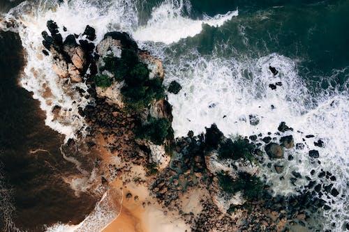 Sea waves splashing over rocky cliff on sunny summer day