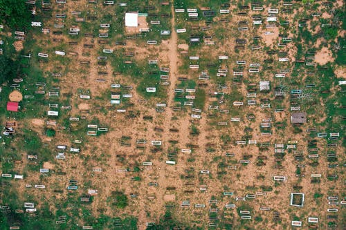 Top view of small trailers and shabby houses in poor suburbs of countryside on sandy terrain in daytime