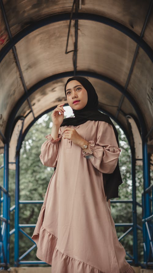 Pensive Muslim woman in trendy long dress and hijab standing in passage placed in park in daytime