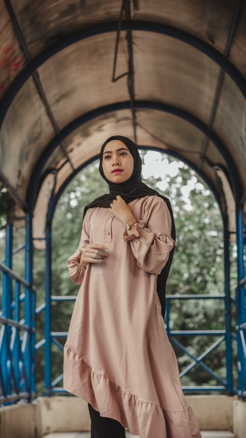Stylish Muslim woman in hijab standing in passage in park
