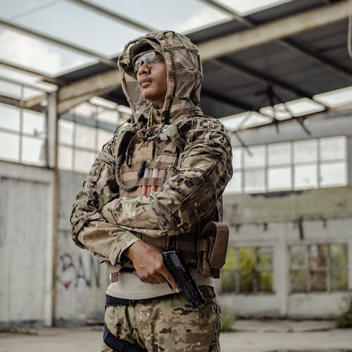 Serious ethnic warrior standing with gun in abandoned building