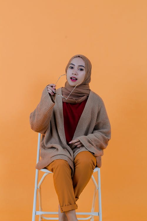 Stylish content Islamic woman putting on sunglasses in studio
