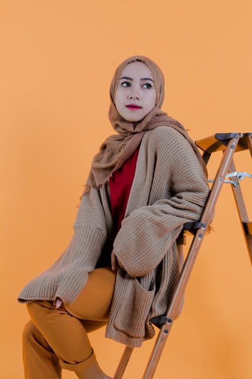 Dreamy stylish Muslim female in headscarf and trendy clothing sitting on stepladder and looking away in photo studio