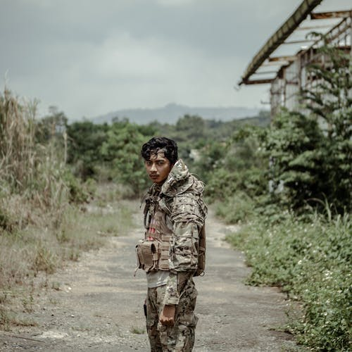 Wistful ethnic soldier standing on footpath in countryside