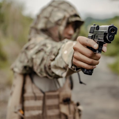 Crop soldier aiming gun in countryside