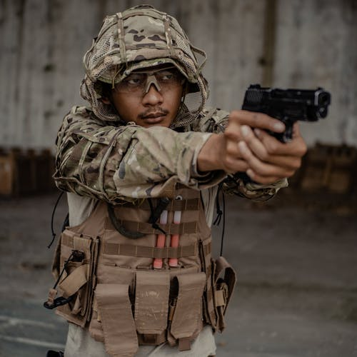 Concentrated ethnic fighter wearing camouflage uniform aiming gun against grunge concrete wall in army shooting range