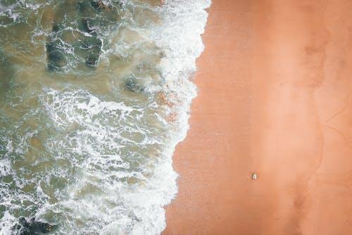 Crystal clear sea water splashing over stones on sandy beach