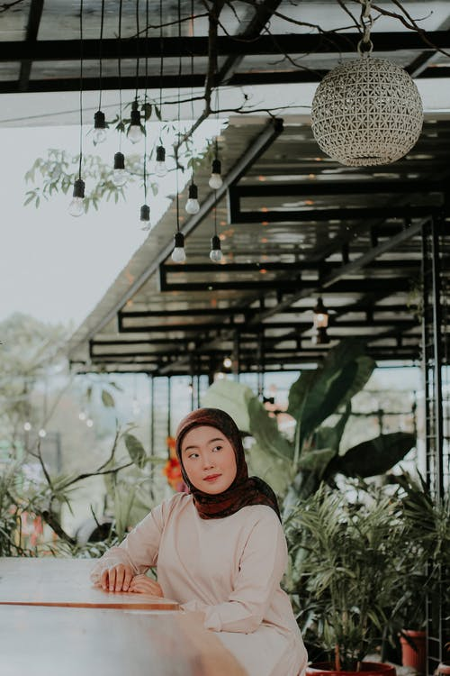 Positive Muslim woman sitting at table in creative cafe