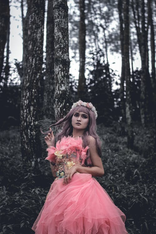 Unemotional young female wearing elegant pink gown and wreath touching hair and looking away thoughtfully while standing in green woodland