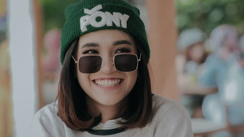 Crop delighted young female in hat and trendy sunglasses standing on street and looking away with toothy smile