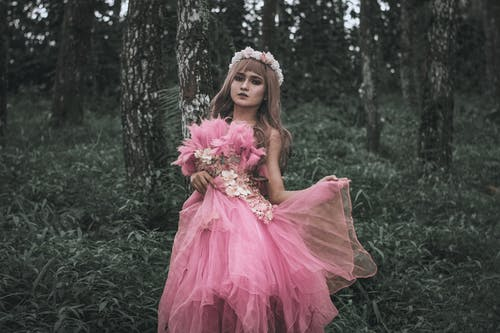 Beautiful woman in chiffon pink dress standing in summer forest