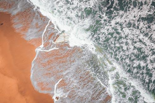 Foamy sea surface with waves splashing on sandy beach