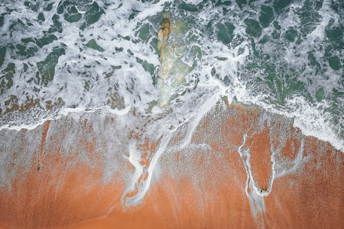 Stormy sea waves washing big stone and sandy coast