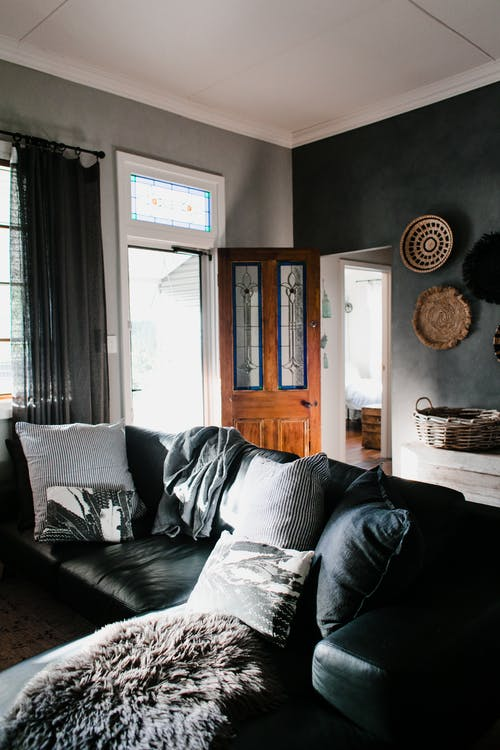 Living Room With Gray and White Throw Pillows on Black Couch