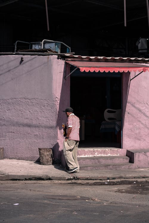 Back view of ethnic man in casual clothes and cap standing near building on street in poor district in sunny day